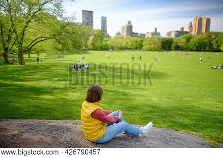 Young Woman Sitting On Large Stone In Central Park In New York On Sunny Spring Day. Sheep Meadows Ar