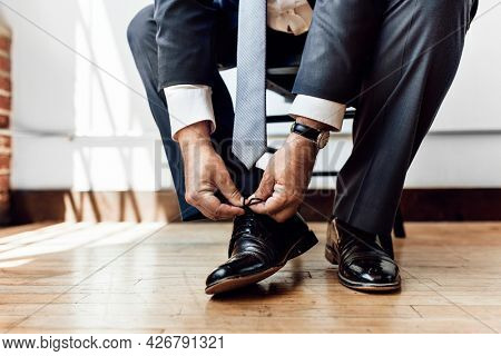 Businessman tying shoe lace before go to work