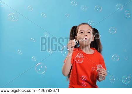 Little Girl Blowing Soap Bubbles On Light Blue Background, Space For Text