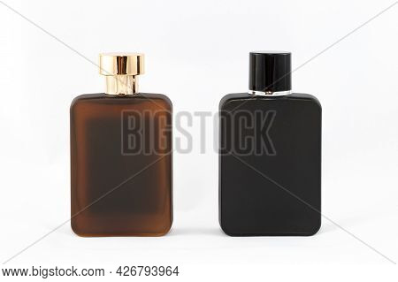 Two Matte Bottles Of Perfume For Men On White Background - Close-up. Black And Brown Blank Glass Spr