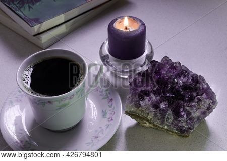 Close Up Of Hot Cup Of Coffee, Amethyst Stone, Candle And Books. Good Vibes For A Relaxing Day.  Pur