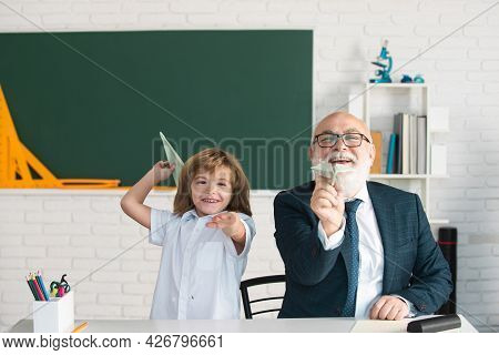 Cute Young Child In Class At School. Senior Teacher And At Home Working. Elderly Teacher Trainer Tee