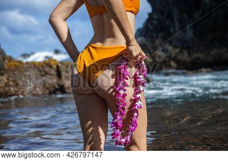 Beautiful Girl With Hawaiian Lei Flower Resting Near Ocean On Beach. Tanned Young Woman On Vacation