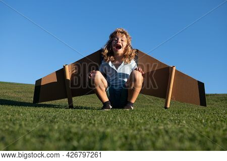 Child Flying In Plane Made Craft Of Cardboard Wings. Dream, Imagination, Childhood. Travel And Summe