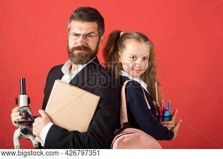 Elementary Pupil With Serious Teacher In Red Studio, Isolated. Portrait Of Funny School Girl And Tut
