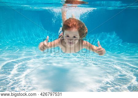 Child Swimming Underwater With Thumbs Up. Underwater Kid Swim Under Water. Child Boy Swimming And Di