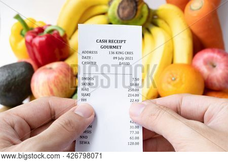 Hands Hold Shopping Receipt Bill With Variety Of Colorful Fresh Fruits And Vegetables. Raw Organic H
