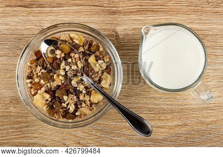 Metallic Spoon In Transparent Glass Bowl Of Granola With Banana And Chocolate, Pitcher With Yogurt O