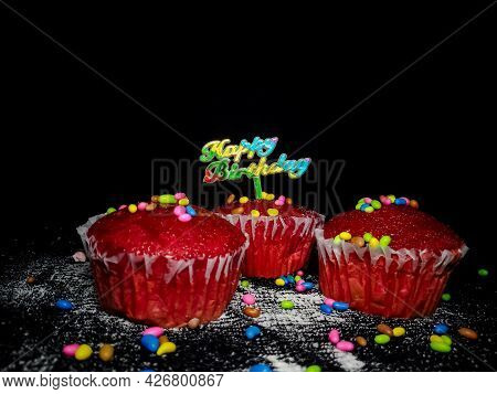 Closeup Of Delicious Red Velvet Birthday Cupcakes Or Muffins Decorated With Sprinkles And Happy Birt