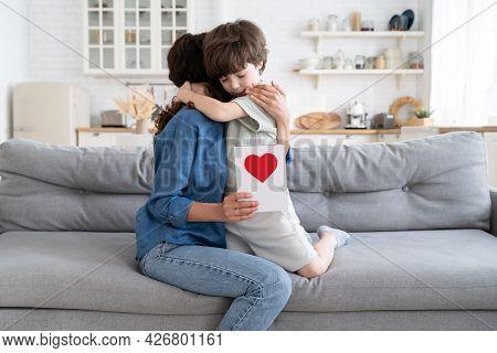 Small Preschool Caucasian Kid Boy Embrace Mom Hold Greeting Card. Little Child Congratulate Mum With