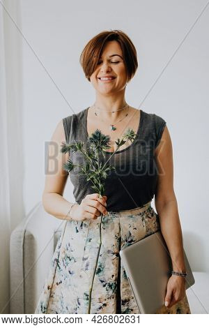 Cheerful woman holding a blue thistle and a laptop