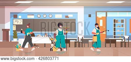 Mix Race Cleaners In Masks Disinfecting Coronavirus Cells In School Classroom To Prevent Covid-19 Pa