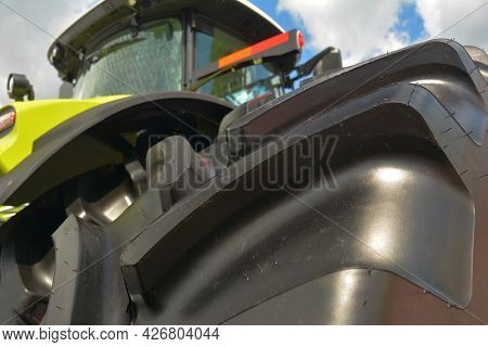 Low Angle View Of A New Farm Tractor With A Close-up Of An Agricultural Tractor Tire.