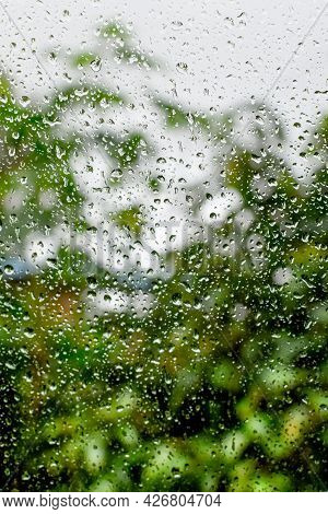 Abstract Background Of Raindrops On The Glass Of Window Of A Car During Monsoon Season With Blurry P