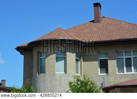 A Close-up Of An Unfinished Stucco Facade Of The House With An Asphalt Shingled Roof, Chimney And Ve