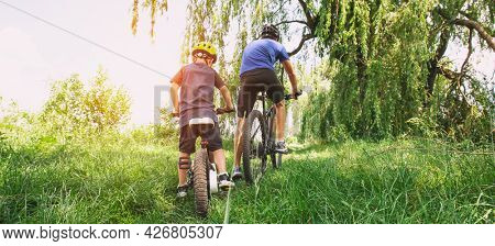 Father and son together are riding bicycles through the pathway