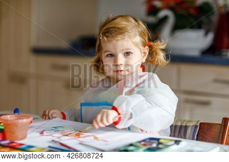 Cute Adorable Baby Girl Learning Painting With Water Colors. Little Toddler Child Drawing At Home, U