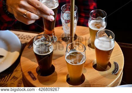 Female Hand Takes Glass Of Craft Beer In Pub To Make Toast Cheers. Drinking Various Types Of Craft B