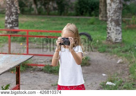 Girl, Blonde, Preschooler, Stands In The Park And Holds A Camera, Portrait Of A Cute Child Of Six Ye