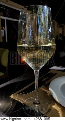 Blurred Sun Flare In Transparent Wine Glass On Tabletop. Glassware For White Wine At Table Setting.