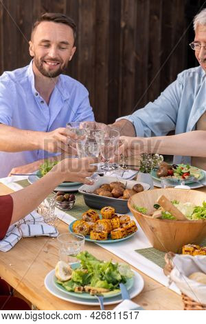 Group of people toasting with glasses of alcohol over dinner table when celebrating birthday, anniverary or other occasion