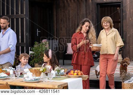 Senior woman and adult daughter discussing basket of fresh bread they are bringing to dinner table