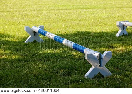 Blue And White Deep Horse Hurdle On A Green Meadow In The Shade, During The Day, Without People, Hor
