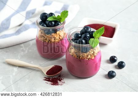 Tasty Dessert With Acai Smoothie, Granola And Berries On Marble Table