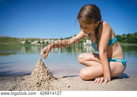 A Little Cute Girl In A Swimsuit Is Building A Sand Castle On The Shore Of A Blue Quarry Lake.