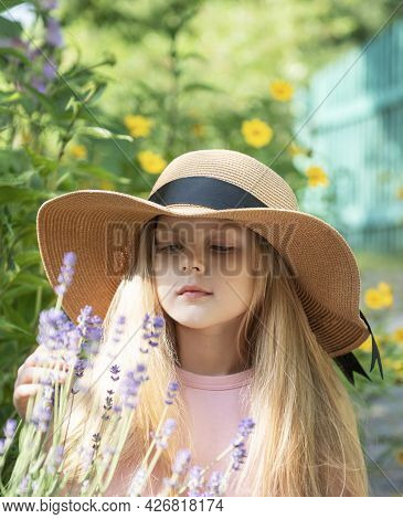 Little Girl In A Straw Hat Surrounded By Lavender Flowers. Portrait Of The Happy Little Girl Blonde
