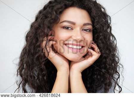 cheerful positive young mixed race female with brunette curly hair, smiling broadly, showing her white teeth at camera