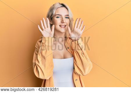 Young blonde girl wearing casual clothes showing and pointing up with fingers number ten while smiling confident and happy.