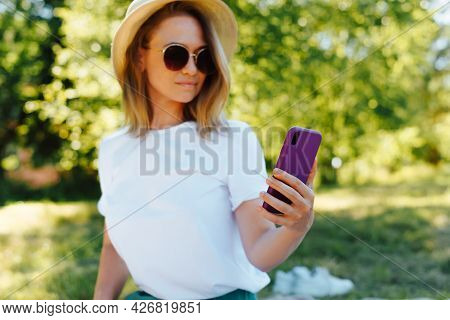 Beautiful Fashionable Young Woman In A Hat And Glasses Taking A Selfie On A Smartphone, Outdoors. Sm