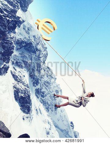 businesswoman climbing mountain with euro on top