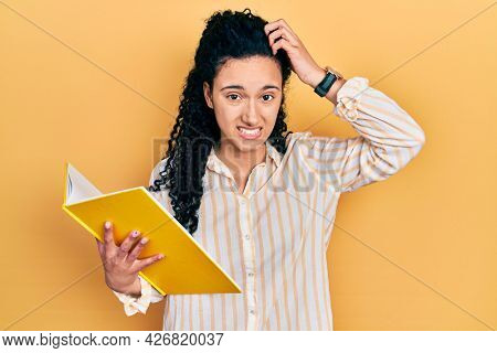 Young hispanic woman with curly hair holding book confuse and wondering about question. uncertain with doubt, thinking with hand on head. pensive concept.
