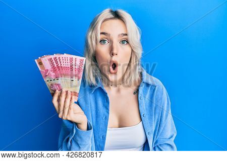 Young blonde girl holding indonesian rupiah banknotes scared and amazed with open mouth for surprise, disbelief face