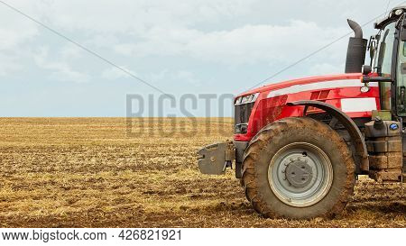 A Tractor In A Field Against The Blue Sky. A Close Photo Of A Modern Red Tractor.