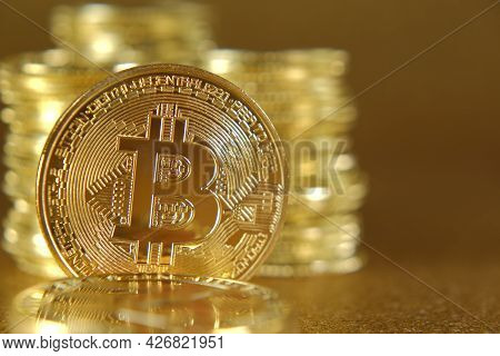 Gold Bitcoin On A Golden Background.virtual Currency. Money And Finance. Blockchain Cryptocurrency.c