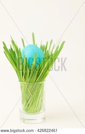A Simple Easter Composition. The Egg, Painted With Bright Paint, Lies In A Stand With Green Grass. W