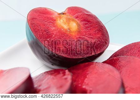 On A White Saucer, A Large Plum, Cut In Half, With Slices Next To It. The Pulp Of Red Berries. Close