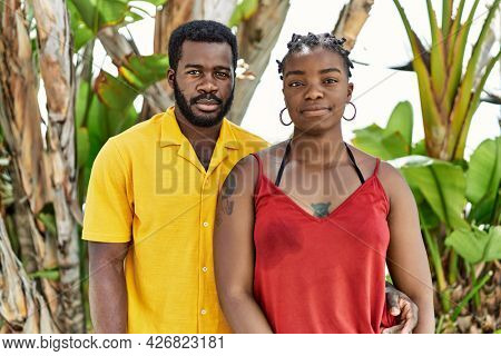 Young african american couple wearing casual clothes standing at the city thinking attitude and sober expression looking self confident