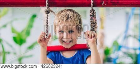 Close Portrait Happy Smile Freckle Blue Eyed Cute Blond Little Boy Sitting On A Rope Ladder, Playing