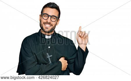 Young hispanic man wearing priest uniform smiling happy pointing with hand and finger to the side