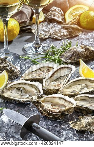 Raw Oysters In Open Shells On Ice With Lemon And White Wine