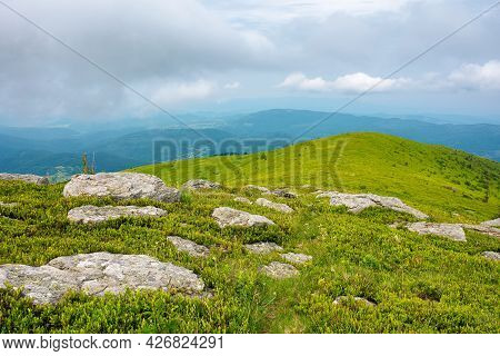 Summer Nature Landscape. Grassy Meadow With Stones On The Hill In Mountainous Scenery Beneath A Clou