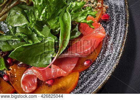 Closeup Of Salad From Persimmon, Salmon, Greens, Pomegranate, Walnuts