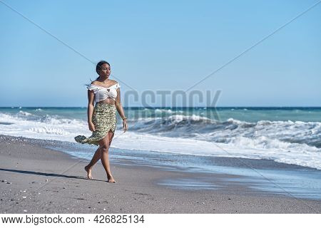 Gorgeous Young African American Woman Strolling Along The Beach In A Summery Skirt