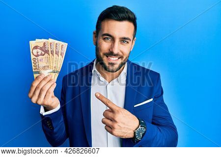 Young hispanic businessman wearing business suit holding hungarian forint banknotes smiling happy pointing with hand and finger