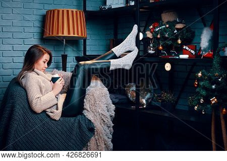 Pretty Woman With Cup Of Cocoa Sitting On Chair. Christmas Tree And Decorations On Shelf. New Years