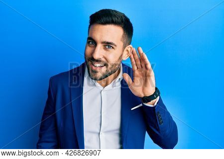 Young hispanic businessman wearing business jacket smiling with hand over ear listening an hearing to rumor or gossip. deafness concept.